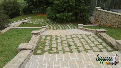 Escada de pedra folheta com as muretas de pedra com as capas e revestimento de pedra, muro e o piso de pedra com juntas de grama em sede da fazenda em Atibaia-SP.