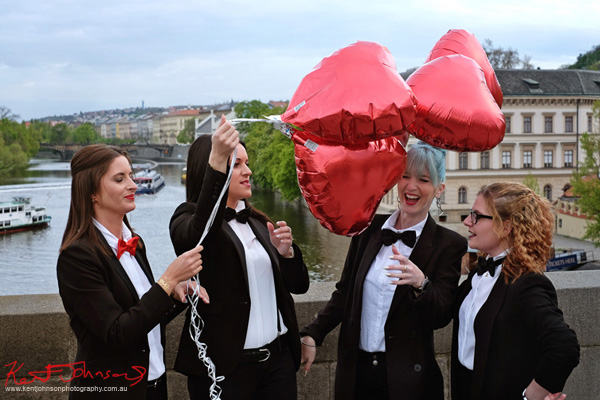 A pre wedding party of womaen on the Charles bridge holding heart shaped balloons. Lifestyle photography in Prague by Kent Johnson.