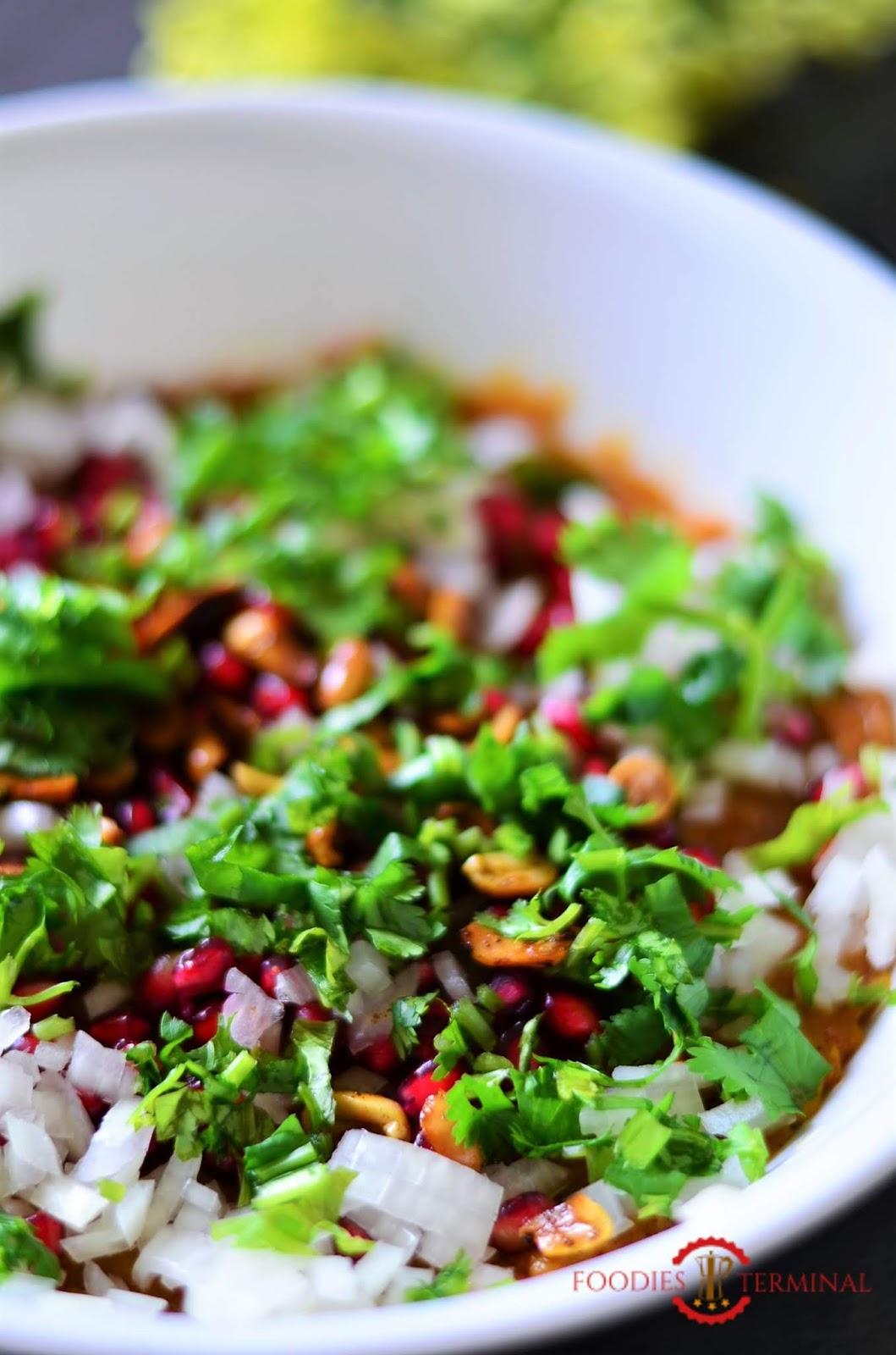 The Potato filling of Kutchi dabeli garmished with fresh pomegranate seeds, masala peanuts, fresh cilantro and chopped onion.