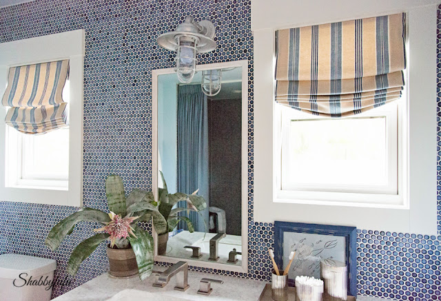 Bathroom in the HGTV Dream Home 2016 - a blue penny tile wall design looks flawless against the bright sunshine.