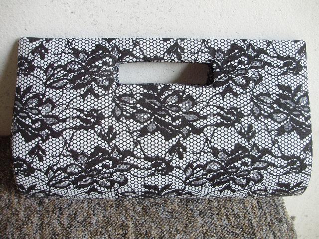 974e1242842e Bolsa Carteira Feita em tecido de algodao. Cor:flores pretas imitando renda,  2 botões internos,alça vasada. Tamanho: 27cm de comprimento e 15cm de  altura.