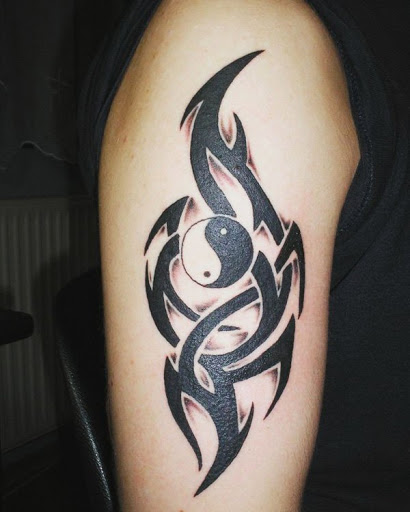 Yin Yang da tatuagem do símbolo armado com símbolos tribais. Esta é uma maneira maravilhosa de fazer o simples Yin Yang tatuagem destacam-se pela adição de complexo e surpreendente padrões tribais.
