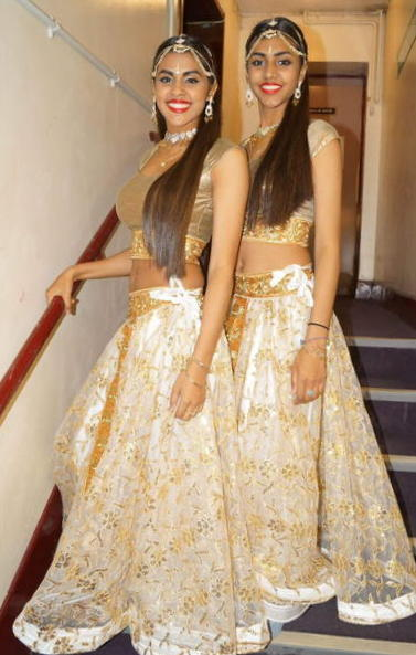 The sisters standing on a stairwell together in their costumes