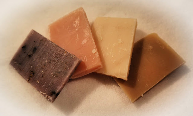 Four small soap rectangles of different colours arranged in a semi circle