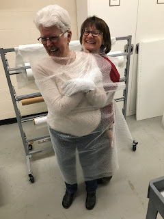 Woman in white shirt and dark pants wears white gloves and is wrapped in bubble wrap. Another woman stands behind her.