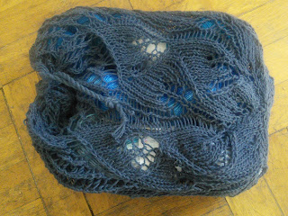 A mesh bag knit in dark yarn. The bottom of the bag is a lace leaf pattern.