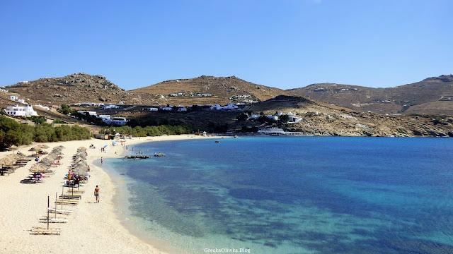 Grecka plaża, Mykonos, Cyklady. Plażowicze, parasole, Słońce, błękitne morze.