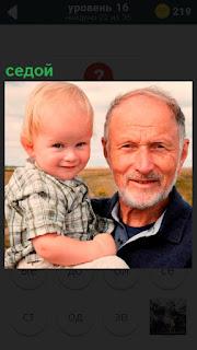 Мужчина седой держит на руках маленького мальчика в поле