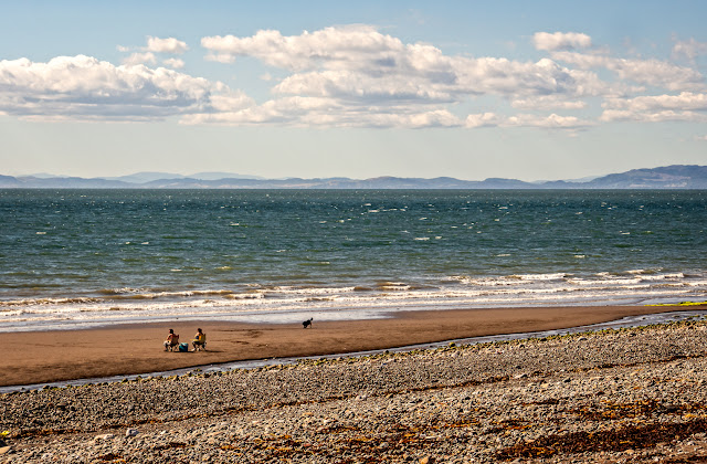 Photo of two people and a dog enjoying a sunny day on Maryport beach