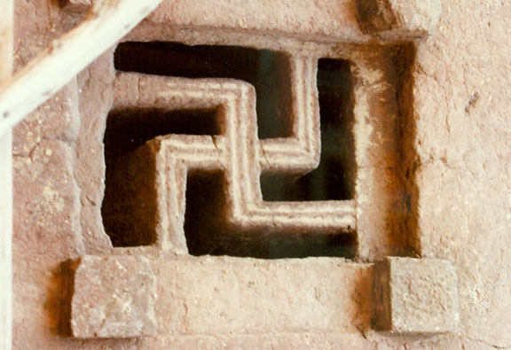 Carved fretwork forming a swastika in the window of a Lalibela Rock-Hewn church in Ethiopia