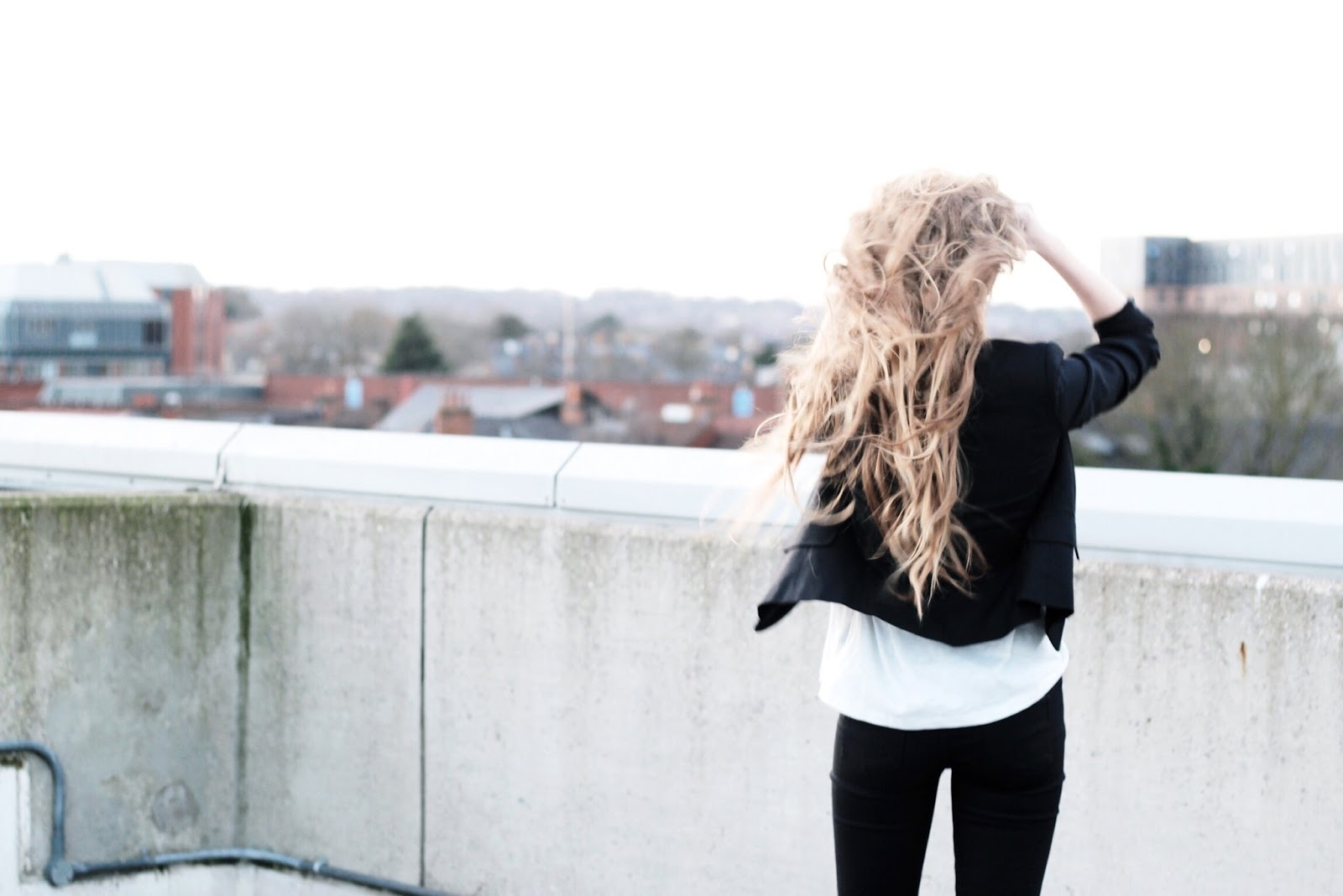 Long Blonde Hair Looking Out Over Cityscape
