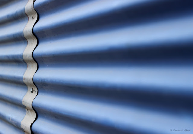 Lines of a Blue Metal Sheet with a vertical wavy strip going across, adding a nice contrast to the overall image