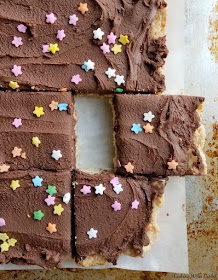 Big sheet of sugar cookie bars with chocolate frosting and sprinkles, some bars cut and one slightly pulled away from the rest
