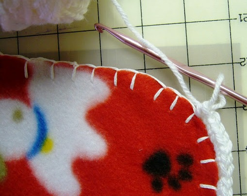 Crocheting edge on fleece blanket in blanket stitch.