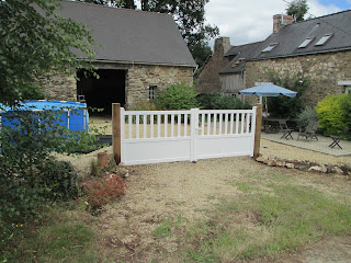 New gates on oak posts with view of the large patio and pool behind