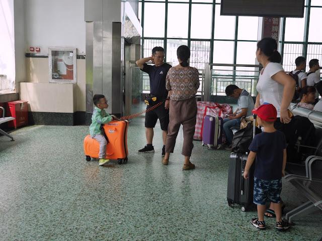 boy sitting on luggage shaped as a seat