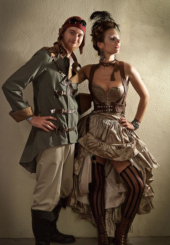Steampunk couple dressed in clothing with muted color palette of taupe and olive green. The woman is dressed as a steampunk showgirl, the man is dressed as a Steampunk Pilot