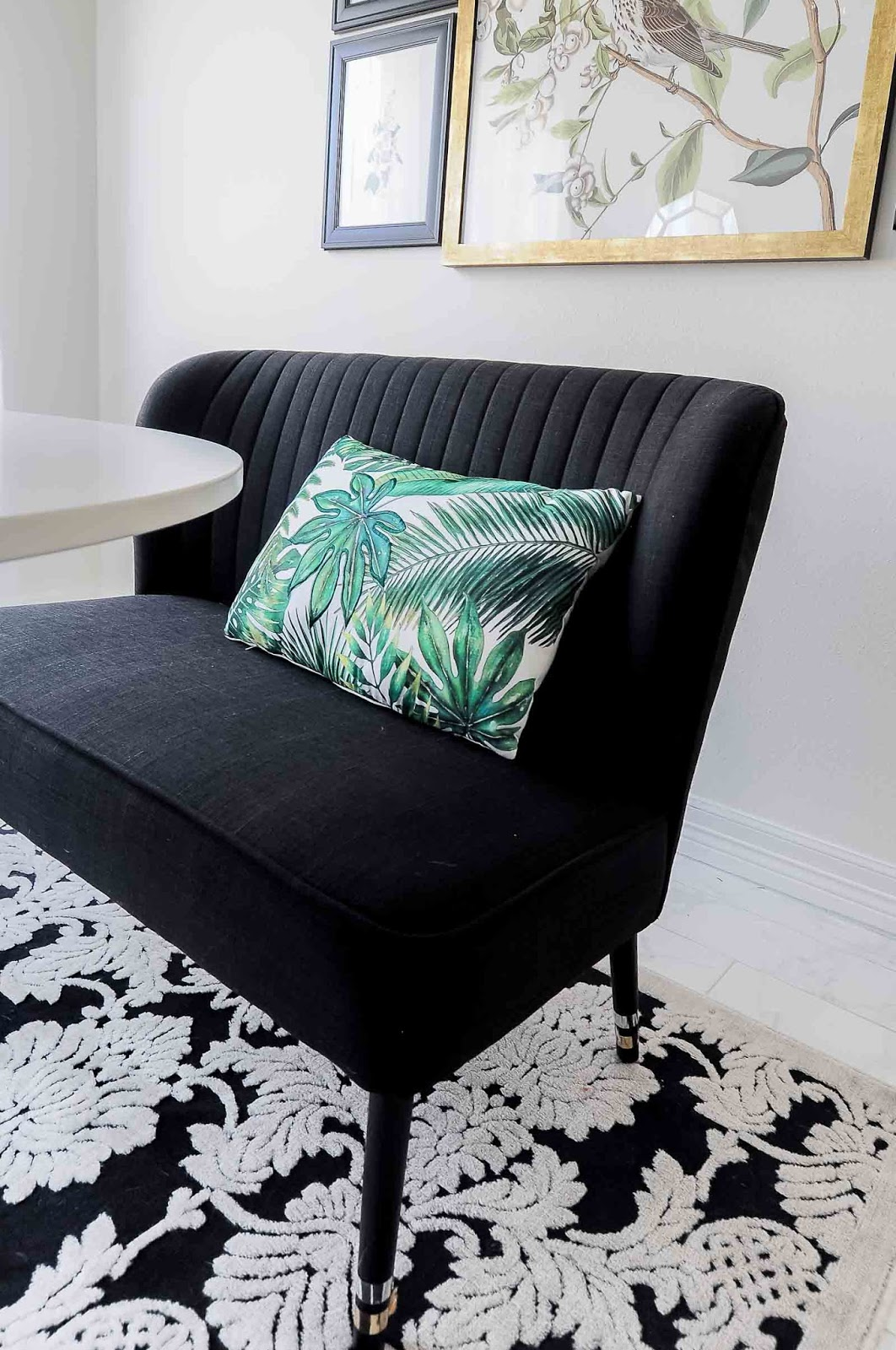 Black bench with a palm leaf pillow and botanical and audubon gallery wall in a dining room space.