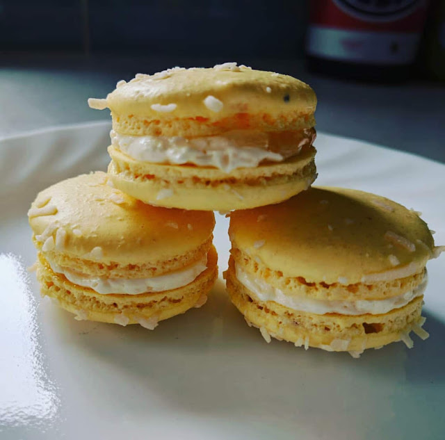three Pina Colada macarons on a white plate.