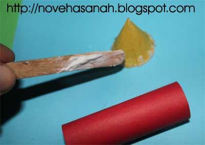 selanjutnya, tambahkan lem secukupnya pada pinggiran untuk nanti disambungkan antara badan roket dengan kepala roket kertas yang berbentuk kerucut ini