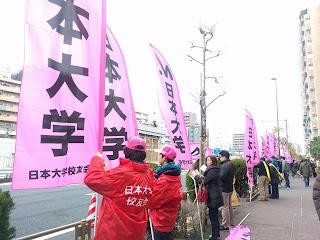 日本大学のピンクの昇りを持って応援する赤いジャンパーの関係者