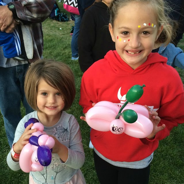 A couple of young sisters posing with thier balloon butterfly and unicorn