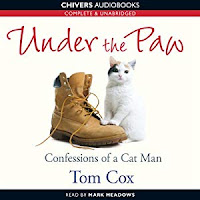 Under the Paw: Confessions of a Cat Man audiobook cover. A white cat with a black patch over its right eye sits beside a workman's boot with its front paws resting on the toe.