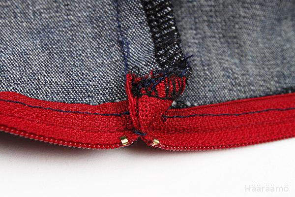 Farkkulaukun vetoketjun päiden kiinnitys saumanvaraan