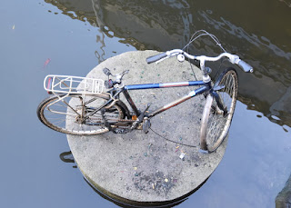Weathered bicycle, double-locked, on a cement pad surrounded by water, Amsterdam, The Netherlands