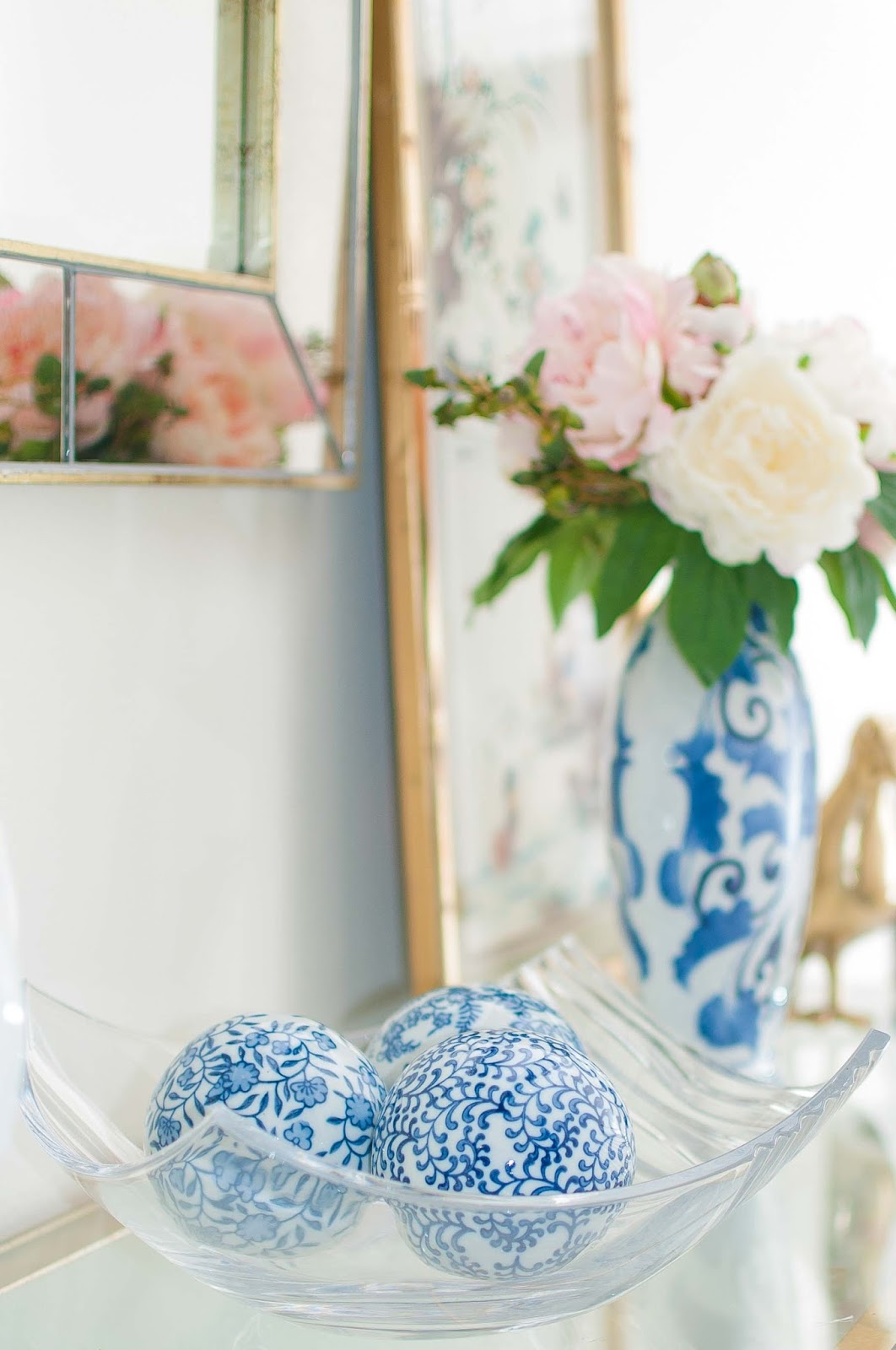 Blue and white decorations on a foyer table with ginger jars and bamboo accents.