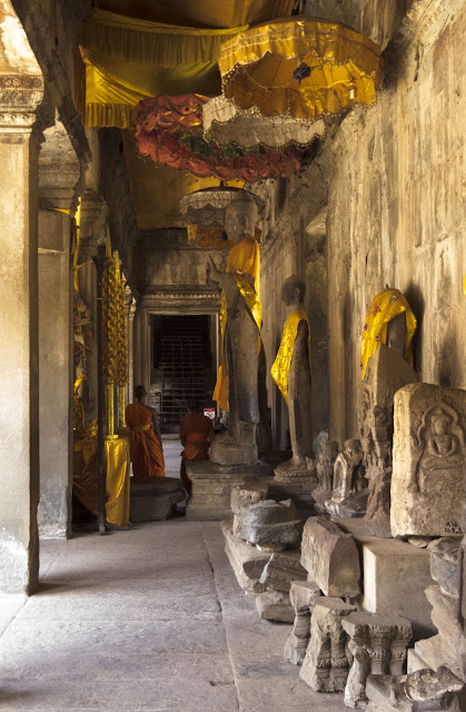 Buddhist monks and statues in Angkor Wat in Cambodia