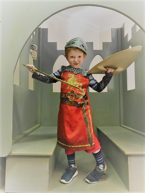 Little boy dressed as a knight holding a sword and shield and pulling a face