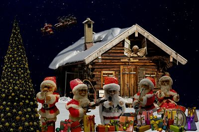 Canciones navideñas. Escena navideña compuesta por pequeñas figuras. Cabaña y árbol de navidad con personajes. Entre ellos, varios Santa Claus tocando instrumentos musicales, y un ángel mirando por la ventana.