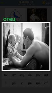 на кровати сидит ребенок и отец его держит двумя руками