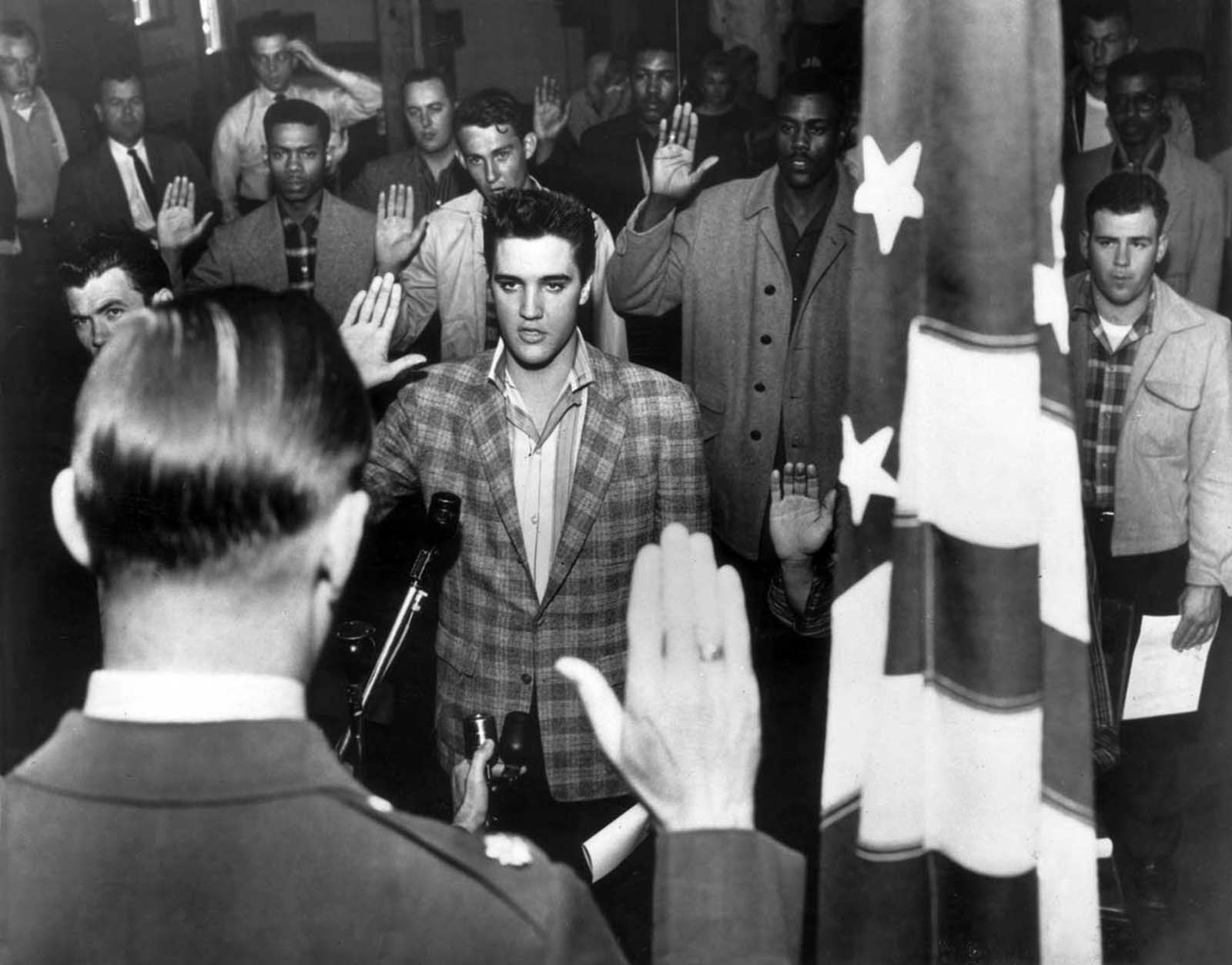 Elvis Presley stands with a group of young men at an induction center, raising their right hands as they are sworn into the United States Army by an officer standing next to an American flag.