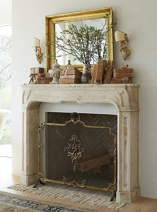 French limestone fireplace with gold leaf mirror, velum books, and Italian sconces #Patinafarm #Frenchfireplace