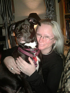 "A happy, large tuxedo ""pit bull"" puppy with a content PatientC."