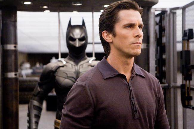 Bruce Wayne delante del traje de Batman