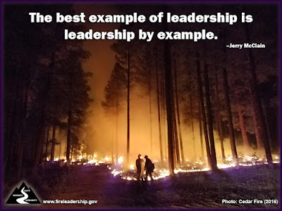 The best example of leadership is leadership by example. –Jerry McClain (Wildland firefighters standing in the forest at night with fire in the background)