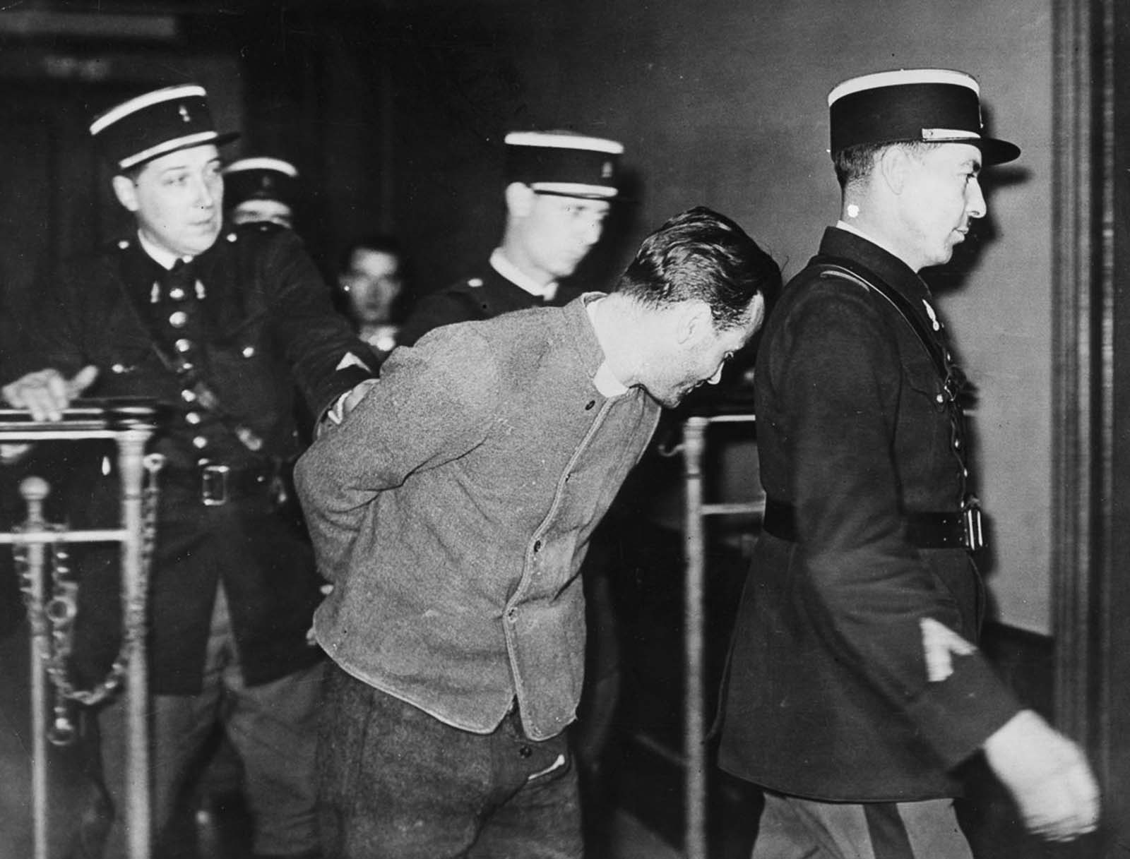 Weidmann is led away in handcuffs after his capture by police.