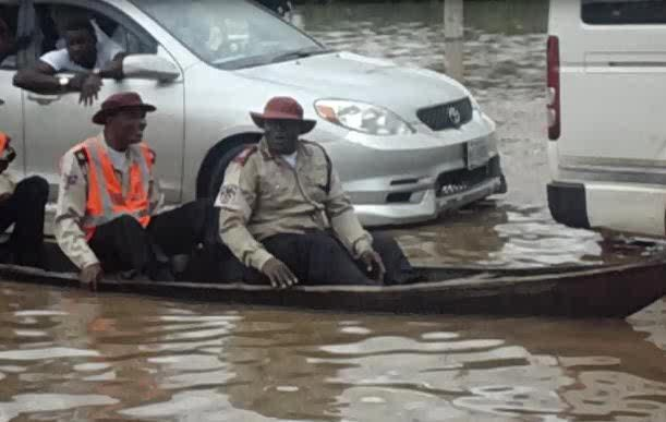 Road safety officials seen riding boat on flooded road