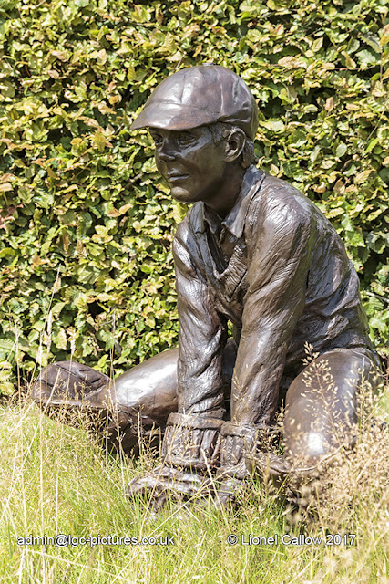 This is an almost life size sculpture of a young boy keeping wicket in bronze