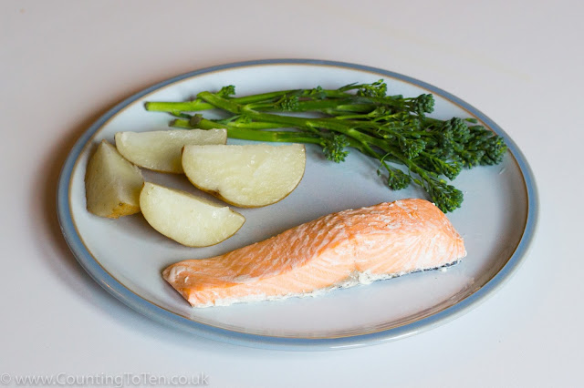A plate of boiled potatoes, broccoli and salmon