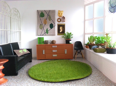 One-twelfth scale modern miniature room with lino floor, white walls and a bay window to the right.There is a black sofa, with an Eames stool next to it, a credenza with art works above it and a black Eames chair to the side of it. The seat of the bay window contains a collection of potted plants.