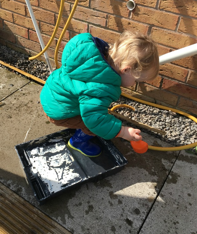 toddler one foot in water in paint tray