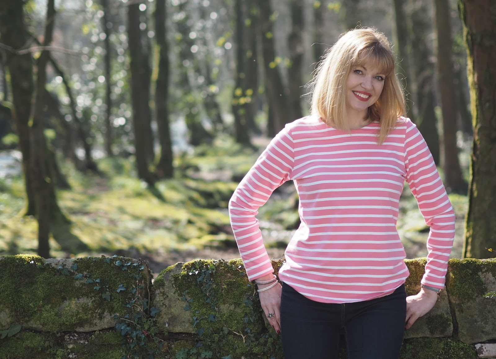 Close up shop of What Lizzy Loves wearing pink and white striped breton top by Tulchan with skinny jeans and silver Superga pumps