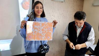 Une des participants montre le résultat du atelier ebru.