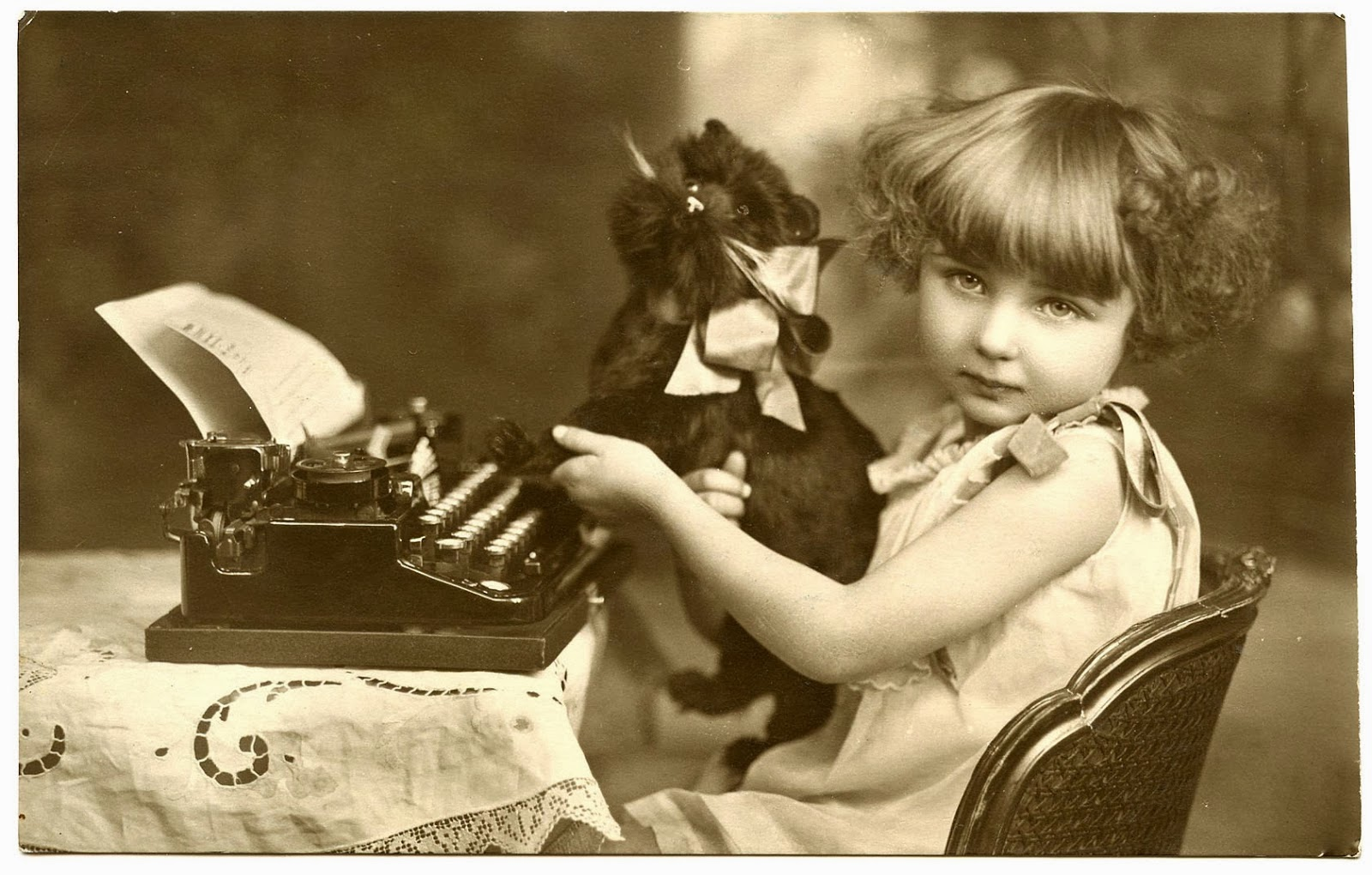 Vintage photo of a small girl siting at a typewriter with a toy cat.