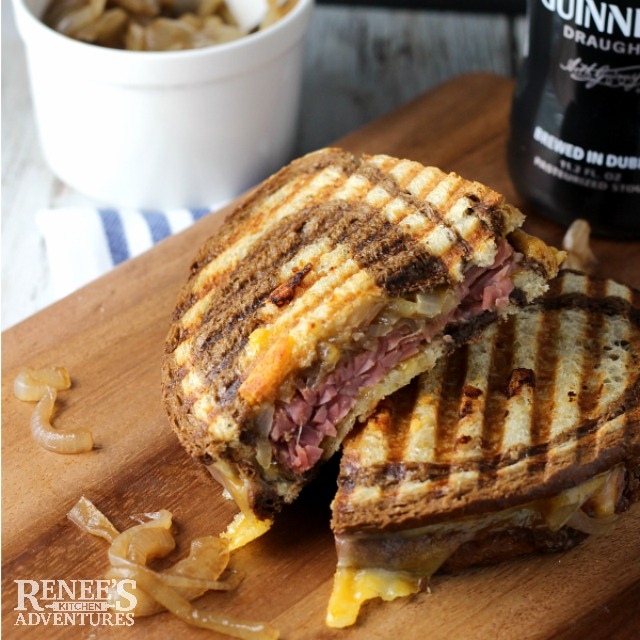 Corned Beef Panini with Caramelized Guinness Onions cut in half and placed one half on top of the other on board