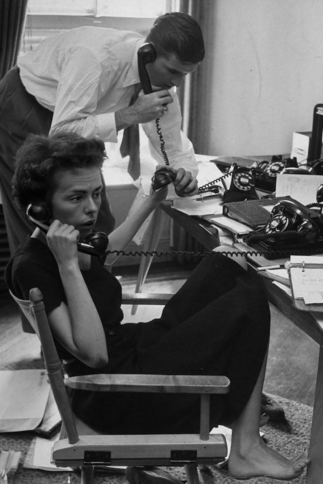 Ford Modeling Agency co-owner Eileen Ford and her husband answering calls requesting one of their 34 high fashion models. They're in her third floor office in New York. She is dressed in black, barefoot and has her hair cut short. 1948.